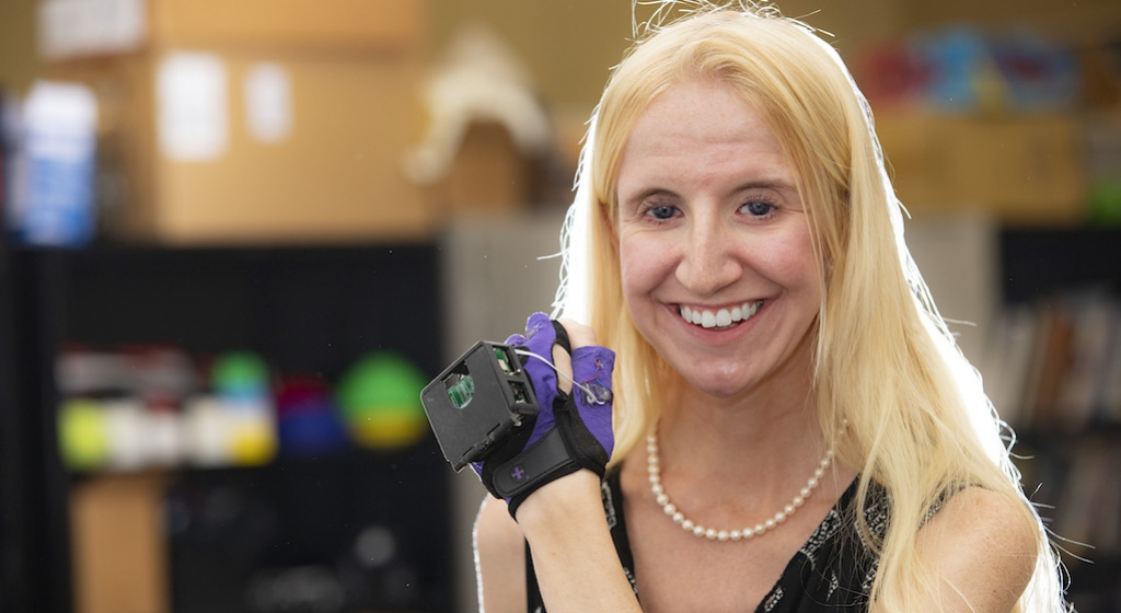 A smiling Caitlyn Seim displays the haptic glove used in her research
